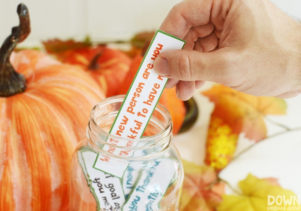 A hand taking a thanksgiving gratitude game card out of a mason jar.