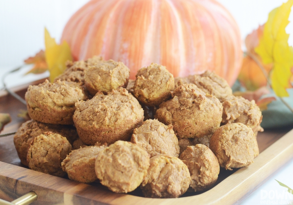 Close up of a pile of freshly baked mini pumpkin muffins.