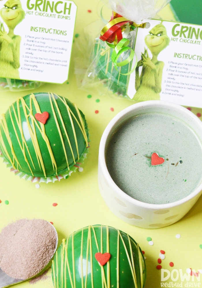 A tall closeup of a cup of hot cocoa made with a Grinch Hot Chocolate Bomb.
