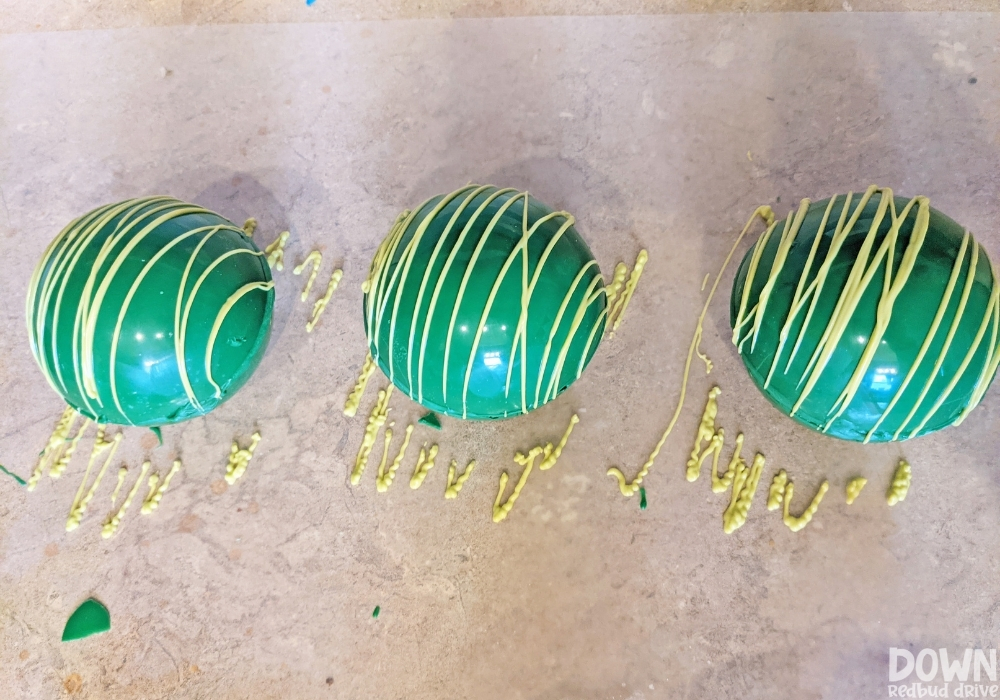 The green hot cocoa bombs with yellow chocolate drizzled on them.
