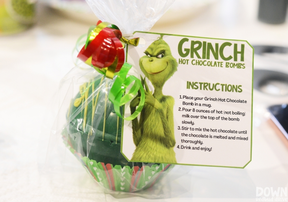 The finished Grinch hot cocoa bomb wrapped with a printable tag attached with ribbon.
