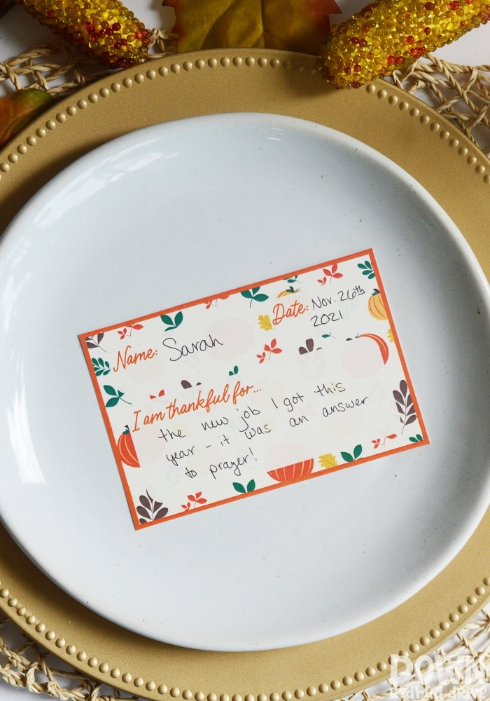 A tall closeup of a filled out Thanksgiving thankful place card.