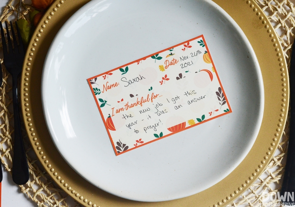A thankful place card filled out on a thanksgiving table.