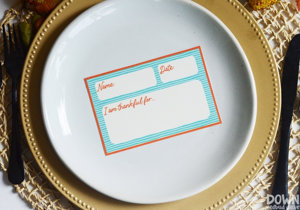 An orange and blue Thanksgiving place card on a plate.