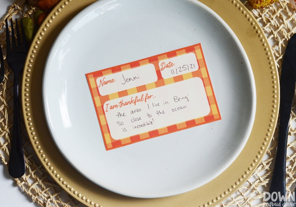 An orange and yellow plaid Thanksgiving thankful place card on a plate.
