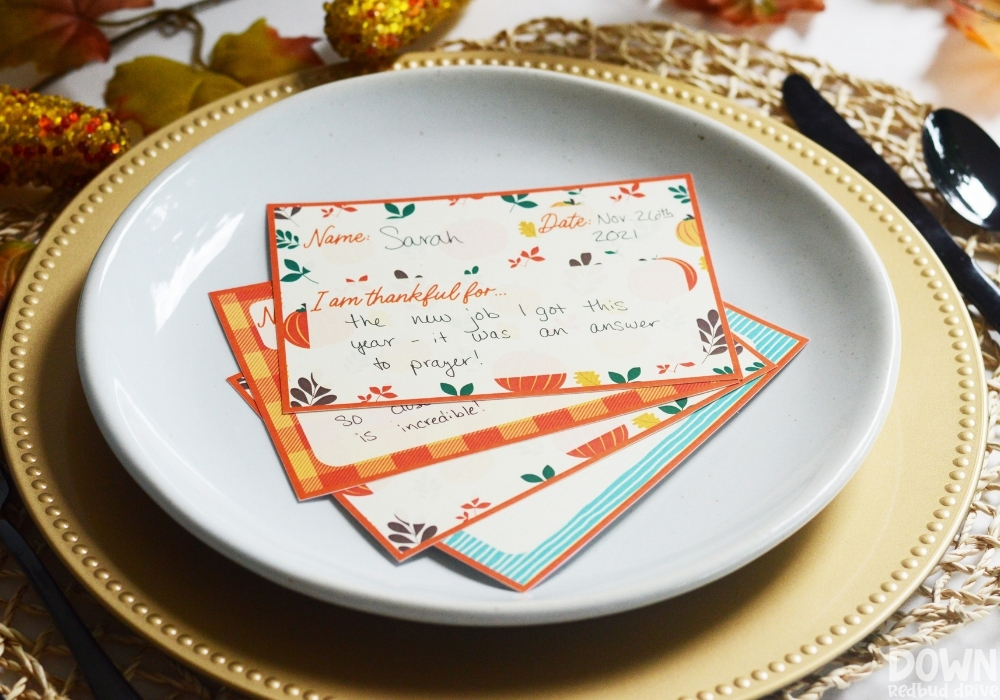 The filled out Thanksgiving thankful place cards fanned out on a plate.